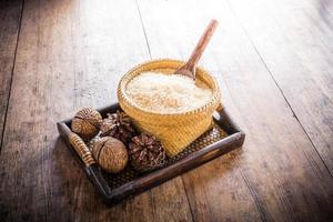 houten lepel in de mand met jasmijnrijst en dennenappels foto