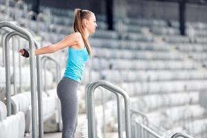fitness meisje uitrekken en gymnastiek oefeningen doen op stadion trappen foto