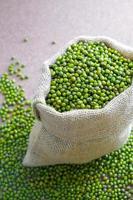gedroogde groene erwten in rustieke zak op houtachtige achtergrond. foto