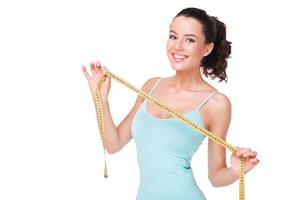 lachende fit vrouw met meetlint foto