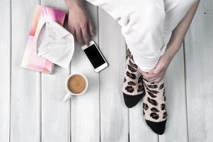 vrouw zittend op de vloer met een smartphone foto