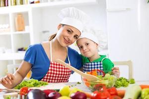 lieve moeder en kind twee chef-koks in de keuken