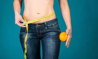 gezond vrouwelijk lichaam met sinaasappel en meetlint. foto