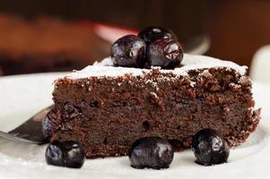 stuk chocoladetaart met bosbessen en poedersuiker