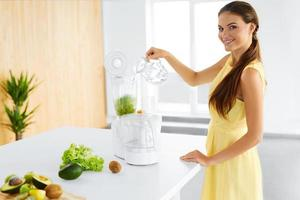 gezond eten. vegetarische vrouw die groen detoxsap voorbereidt. eetpatroon foto