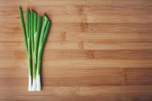 groene uien op een houten foto