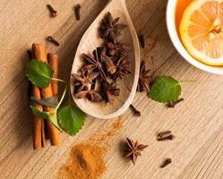 anijssterren, thee en kaneelstokjes op hout foto