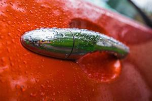 handvat oranje auto is nat foto