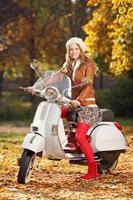 portret van mooie jonge vrouw op scooter foto