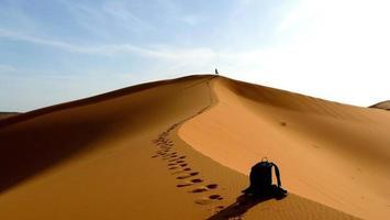 klimmen naar de top van een grote zandduin foto