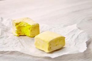smakelijke twee vierkante gele pastel marsmallows op ambachtelijk papier, bijten foto
