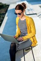 vrouw met laptop en telefoon buitenshuis foto