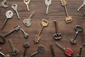veel verschillende sleutels op houten tafel foto