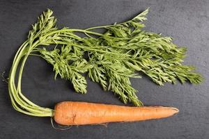 verse wortelen op zwarte leisteen foto