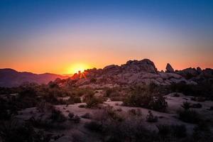 opkomst van de zon boven rotsformatie in Joshua Tree National Park foto