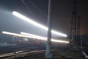 nachttreinstation en verlichte spoorweg in de stad foto