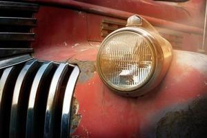 vintage roestige rode vrachtwagenauto met een nieuwe koplamp foto