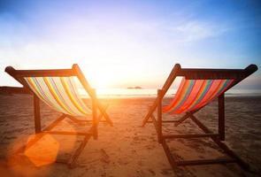 ligstoelen op de verlaten kustzee bij zonsopgang. foto