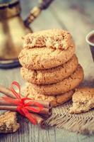 zelfgemaakte haverkoekjes, kaneelstokjes en koffie foto
