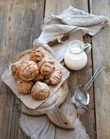 kaneelbroodjes met suikerpoeder op rustieke houten plank, kruik foto