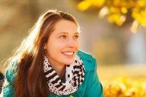 mooi meisje dat in de herfstbladeren ligt