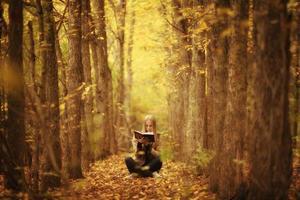 jong mooi meisje met een boek in de herfst bos