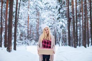 meisje met een kerstcadeau in winter woud foto