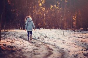 kind meisje lopen de weg in winter woud foto