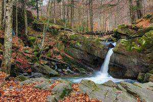 prachtige waterval komt uit een enorme rots in het bos foto