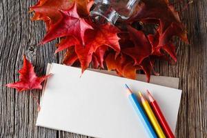 open notitieboekje. vallen op bladeren op verweerde tafel