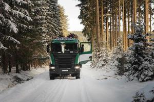 vrachtwagen met inloggen weg in bos in de winter foto