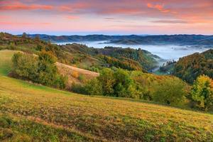 kleurrijke herfst bos en mist holbav dorp, transsylvanië, roemenië, europa foto