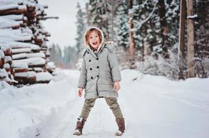 kind meisje op gezellige warme buiten winterwandeling in het bos foto