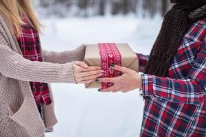 meisje geeft haar vriend een geschenk in het winterbos foto