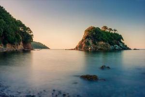 klein rotsachtig eiland terwijl zonsopgang bij oceaan in Italië