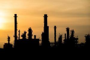 silhouet van olieraffinaderij bij zonsondergang
