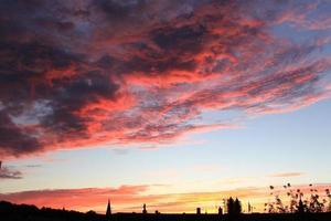 bloedige zonsondergangwolken boven de stad foto