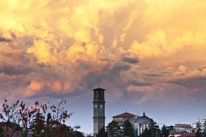 avond storm cloudscape tegen klokken toren foto