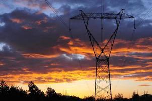 elektrische bovengrondse transmissielijn toren bij dageraad foto