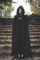 mooie donkere vampiervrouw met zwarte mantel en kap foto