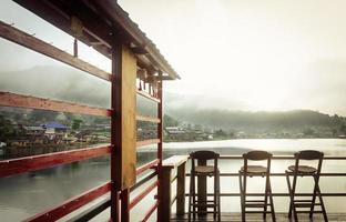 drie bamboe stoelen op een prachtig meer in de ochtendtijd foto