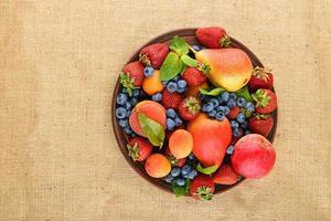 fruit en bessen mix in keramische plaat op jute canvas foto