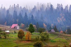 oude houten hutcabine in berg bij landelijke herfstlandschap foto