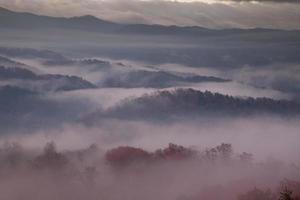 rood getinte ochtendmist boven rokerige bergen
