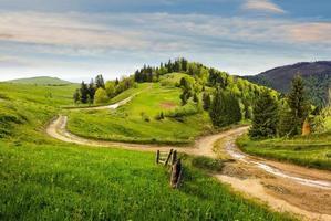 kruispunt op heuvel weide in de bergen bij zonsopgang foto