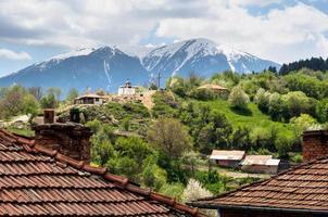 Bulgaars bergdorp, kleine kapel en sneeuwberg foto