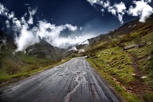 Bergweg. weg tussen bergen met bomen en blauwe lucht