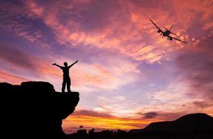 silhouet van een man op de rots en het vliegtuig foto