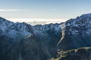 zee van wolken achter de bergkam