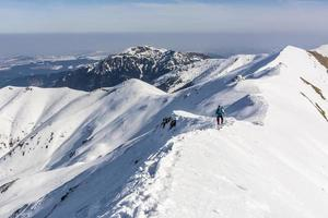 bergbeklimmer op de bergkam in winterse omstandigheden